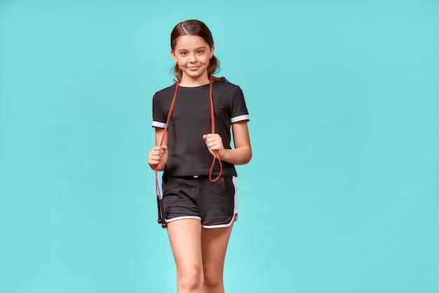 Dzieci zaangażowane w sport ładna nastolatka w czarnej odzieży sportowej ze skakanką patrzącą na kamerę