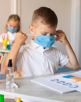 Dzieci zakładają jego maskę medyczną