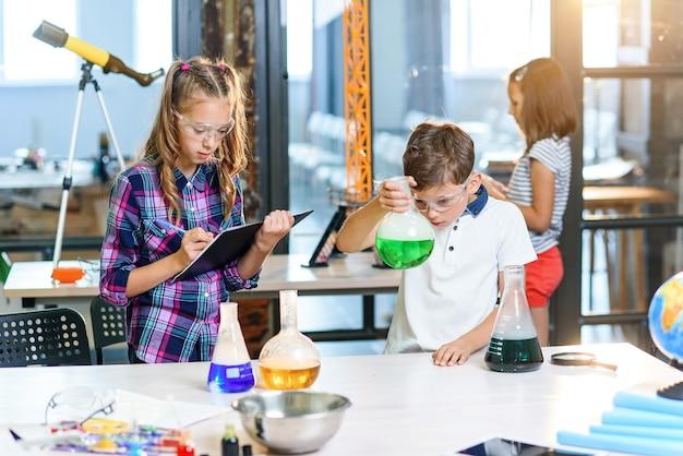 Dzieci zapisują wyniki eksperymentów w zeszycie. dwóch młodych sprytnych uczniów rasy kaukaskiej w okularach ochronnych robi eksperyment z zielonym płynem w zlewce i suchym lodzie.