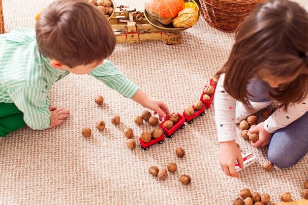 Dzieci zbierają orzechy w zabawkowym pociągu i uczą się liczyć siedząc na podłodze w przedszkolu. koncepcja pociągu towarowego