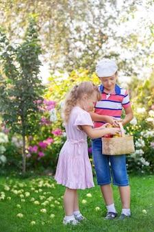 Dzieci zbierają owoce w ogrodzie