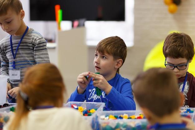 Dzieci zbierają różne przedmioty z plastikowych części konstruktora w szkole technologii cyfrowych