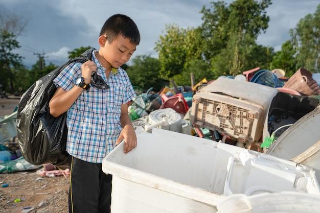 Dzieci zbierają śmieci do czarnej torby na plastikowym stosie
