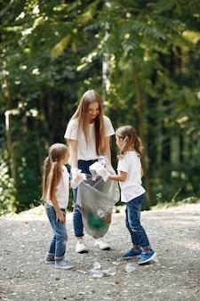 Dzieci zbierają śmieci w workach na śmieci w parku