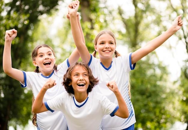 Dzieci zdobywają trofeum po wygraniu meczu piłki nożnej na zewnątrz