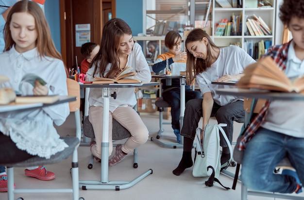Dzieci ze szkoły podstawowej siedzą na biurkach i czytają książki w klasie. młoda dziewczyna próbuje znaleźć swoją książkę w plecaku.