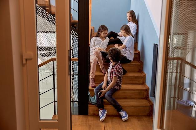 Dzieci ze szkoły podstawowej siedzą na schodach podczas przerwy w szkole.