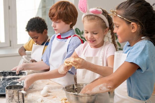 Dzieci zebrały się w nowoczesnej kuchni i studiowały przepis na pyszny deser, zastanawiając się nad świątecznym menu na dzień matki