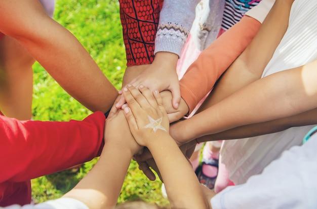 Dzieci złożyły razem ręce, bawiące się na ulicy