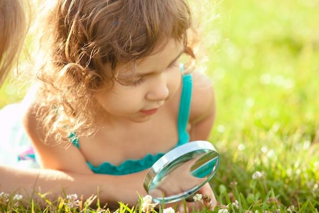 Dzieciak bawi się lupą w ogrodzie