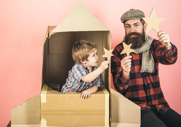 Dzieciak bawi się papierową gwiazdą w kosmicznej rakiety chłopiec bawi się tekturową rakietą syn bawi się z ojcem