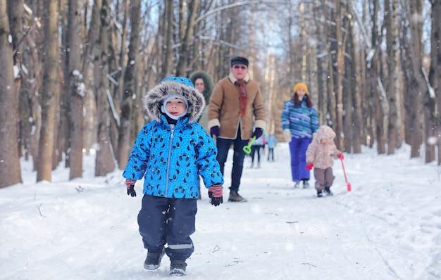 Dzieciak bawi się w zimowym parku i baw się z rodziną