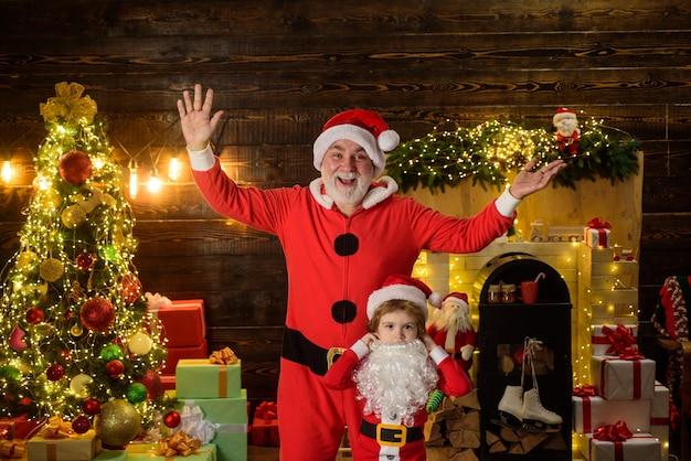 Dzieciak chłopiec i ojciec w stroju świętego mikołaja i brodzie święty mikołaj i dziecko z prezentem świątecznym