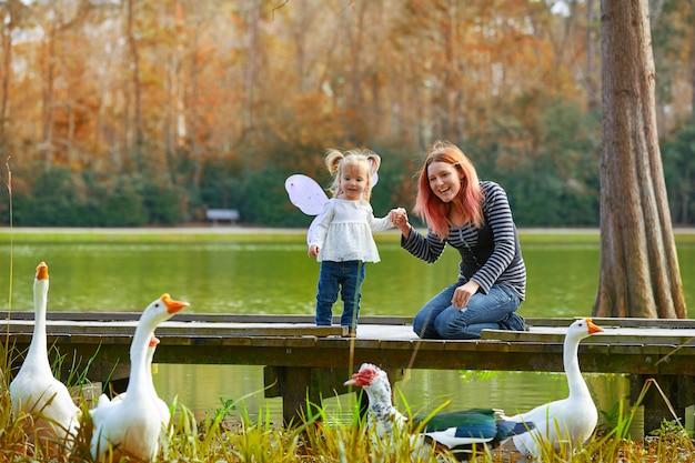 Dzieciak dziewczyna i matka bawić się z kaczkami w jeziorze
