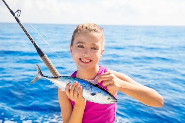 Dzieciak dziewczyna łowi tuńczyka małego tuńczyka szczęśliwego z rybim chwytem