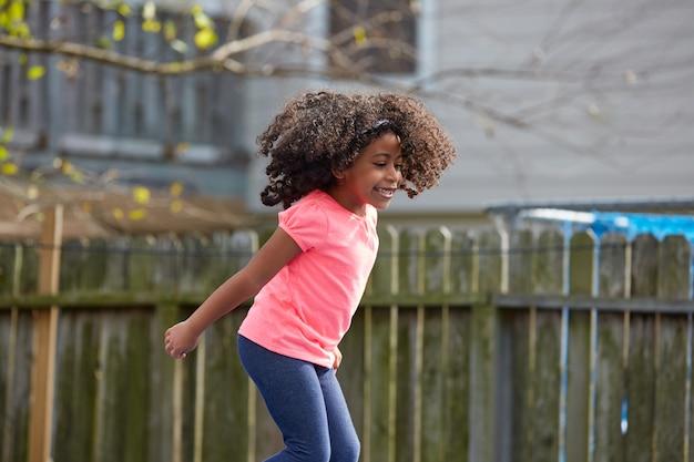 Dzieciak dziewczyna maluch skoki na placu zabaw