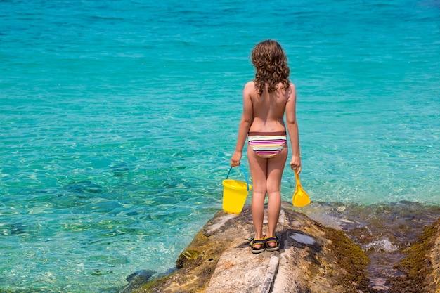 Dzieciak dziewczyna tylni widok w plażowej tropikalnej turkus wodzie