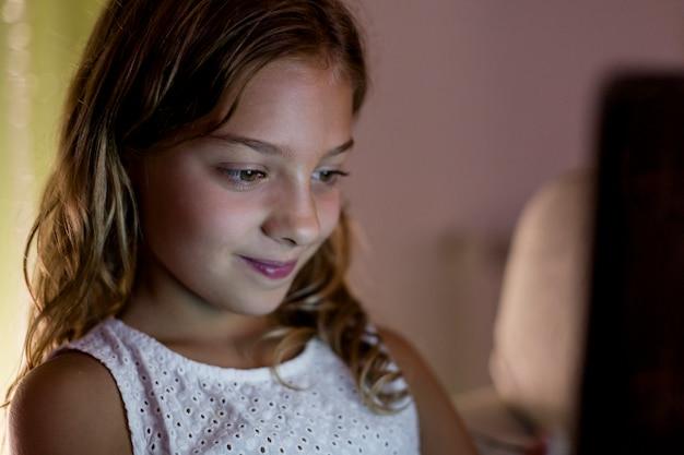 Dzieciak dziewczyna używa pastylkę w domu. koncepcja technologii. rodzinny styl życia w pomieszczeniu