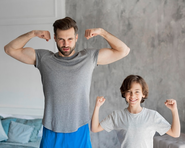 Dzieciak i jego ojciec uprawiają sport w domu