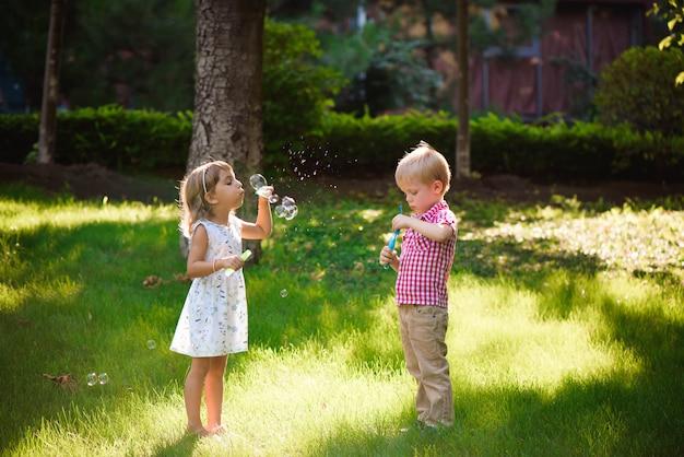 Dzieciak i przyjaciele grają w bańki na placu zabaw o zachodzie słońca