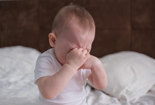 Dzieciak jest zdenerwowany. dziecko siedzi na łóżku i płacze