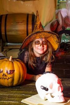 Dzieciak mała dziewczynka w kostiumie na halloween na imprezie halloweenowej halloween słodycze śmieszne dziecko z dynią ...