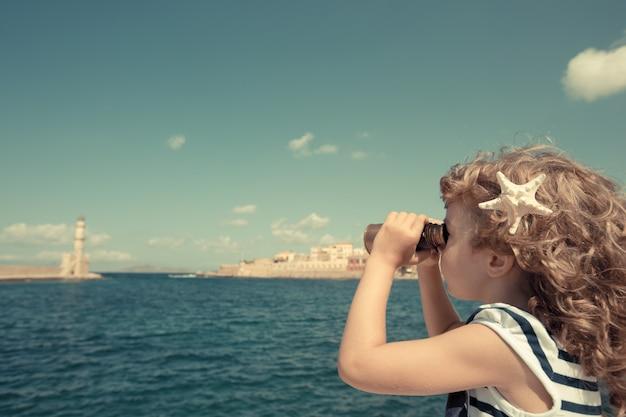 Dzieciak marynarza patrzący przez lornetkę na tle błękitnego nieba