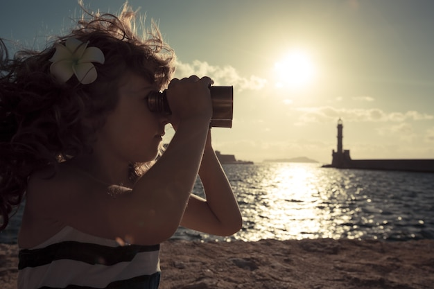 Dzieciak marynarza patrzący przez lornetkę przed zachodem słońca