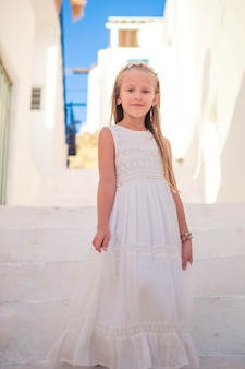 Dzieciak na ulicy typowej greckiej tradycyjnej wioski z białymi ścianami i kolorowymi drzwiami na wyspie mykonos