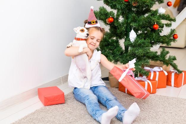 Dzieciak otwierający prezenty świąteczne. dziecko pod choinką z pudełkami na prezenty.