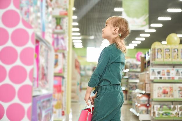 Dzieciak patrzeje półki z zabawkami w sklepie.