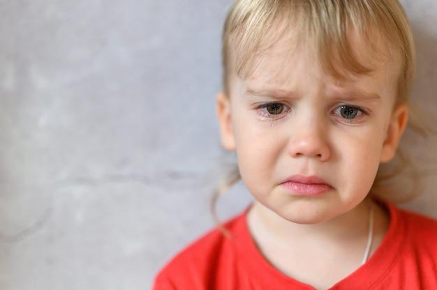 Dzieciak płacze. twarz ślicznego, zmartwionego czteroletniego chłopca we łzach. smutek dzieci. szary tło ścian betonowych. miejsce na tekst