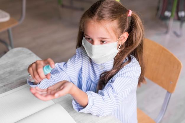 Dzieciak pod wysokim kątem dezynfekujący jej ręce