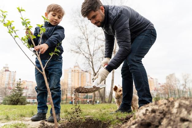 Dzieciak próbuje zasadzić drzewo na zewnątrz