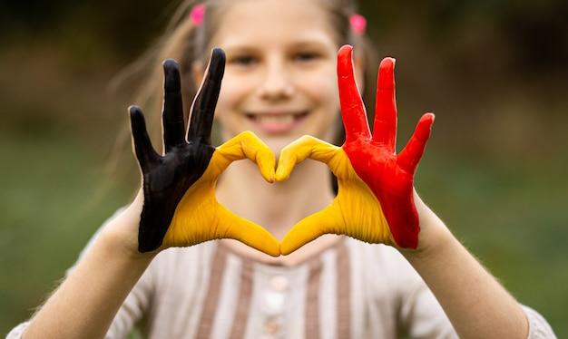 Dzieciak ręce malowane w kolorze flagi belgii pokazują symbol gestu serca i miłości