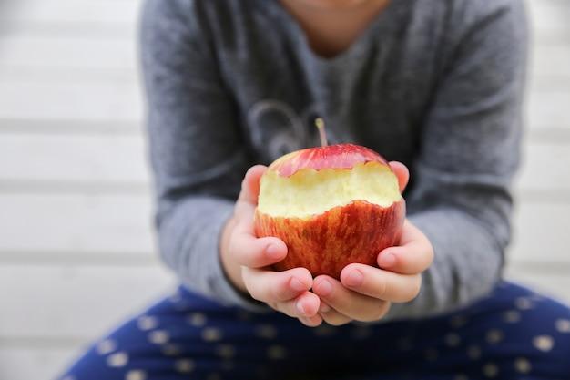 Dzieciak ręki trzyma czerwień gryźć jabłka, zdrowia pojęcie