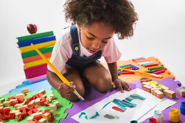 Dzieciak rysuje na sztuki macie w studiu