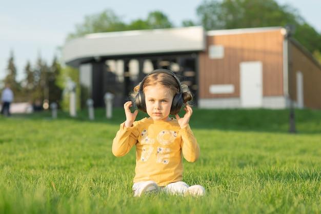 Dzieciak słuchaj muzyki w słuchawkach ciesz się piosenką w radiu siedź na zielonej trawie łące na liście odtwarzania parksummer