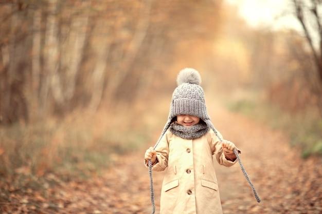 Dzieciak spacerujący jesienią w parku uśmiechnięty szczęśliwe dziecko dziewczynka ubrana w szary ciepły dzianinowy pompon i szalik