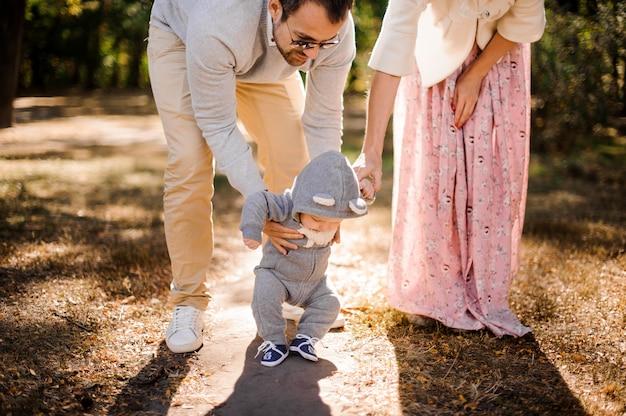 Dzieciak stawia pierwsze kroki, trzymając się za ręce taty i matki