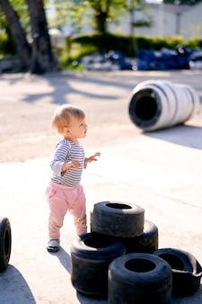 Dzieciak stoi bokiem w pobliżu spiętrzonych opon samochodowych na parkingu