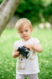 Dzieciak stoi na zielonym trawniku i trzyma w rękach samochodzik