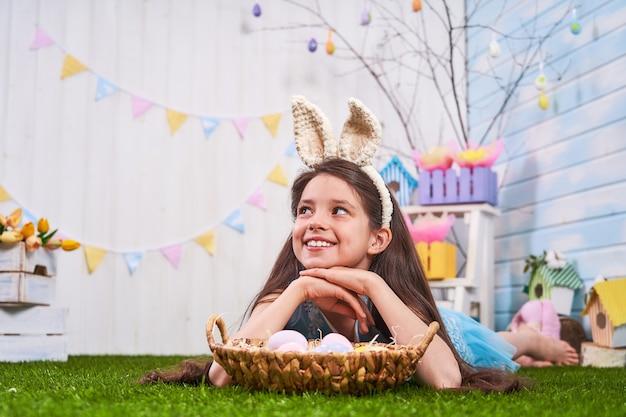 Dzieciak świętuje wielkanoc. śmieszne szczęśliwe dziecko w uszach królika, grając z pisanki