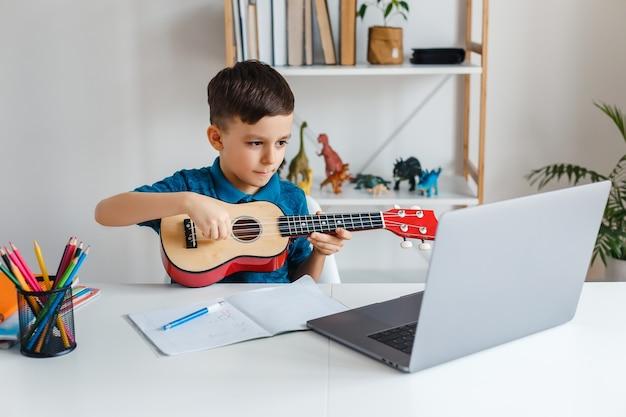Dzieciak szuka lekcji wideo online o sopranowym ukulele za pośrednictwem laptopa via