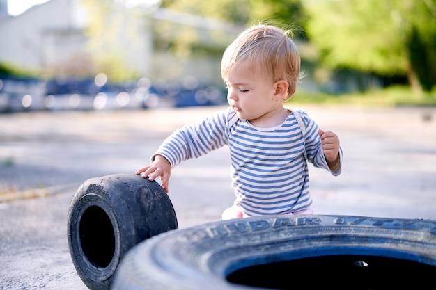 Dzieciak trzyma felgę samochodu na parkingu