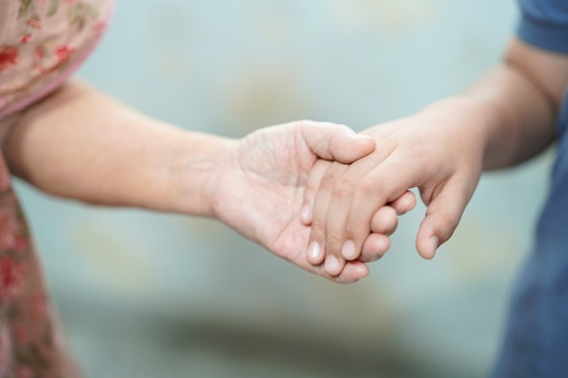 Dzieciak trzyma rękę azjatycki starszy lub starszej starszej pani pacjenta