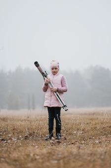 Dzieciak trzyma teleskop na zewnątrz