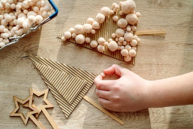 Dzieciak trzyma w rękach dekorację choinkową. dzieciak pokazuje dekorację choinkową. zero marnowania