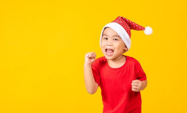 Dzieciak ubrany w czerwony kapelusz świętego mikołaja portret azjatyckiego małego słodkiego chłopca uśmiech i podekscytowany