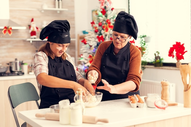 Dzieciak ubrany w fartuch mieszający ciasto w boże narodzenie